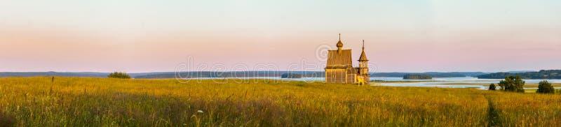 Ξύλινη εκκλησία στην κορυφή του λόφου Άποψη του χωριού ηλιοβασιλέματος Vershinino Περιοχή του Αρχάγγελσκ, της βόρειας Ρωσίας στοκ εικόνα