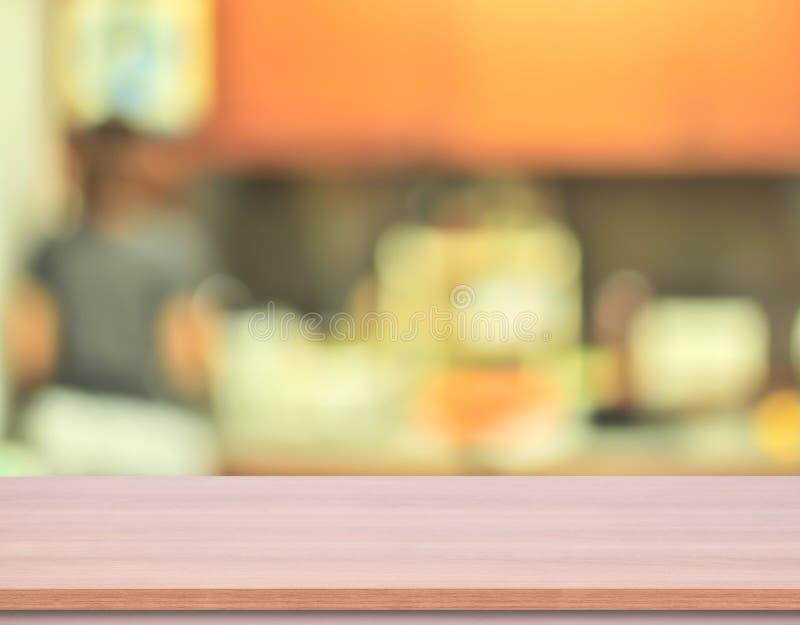 Ξύλινη επιτραπέζια κορυφή κουζινών με το υπόβαθρο κουζινών θαμπάδων στοκ φωτογραφία με δικαίωμα ελεύθερης χρήσης