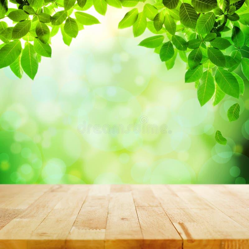Ξύλινη επιτραπέζια κορυφή με το πράσινο υπόβαθρο φύλλων & θαμπάδων bokeh στοκ φωτογραφίες