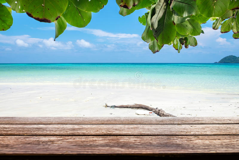 Ξύλινη επιτραπέζια κορυφή στη ζωηρόχρωμη άσπρη άμμο παραλιών θάλασσας στοκ φωτογραφίες