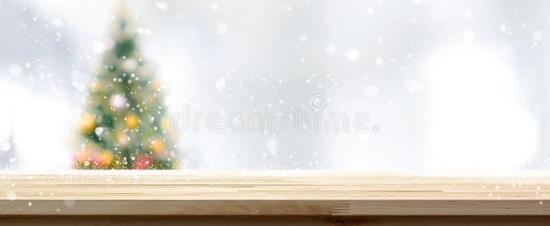 Ξύλινη επιτραπέζια κορυφή στο υπόβαθρο εμβλημάτων χριστουγεννιάτικων δέντρων θαμπάδων στοκ φωτογραφίες