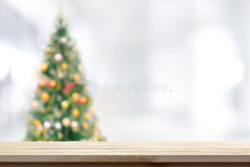 Ξύλινη επιτραπέζια κορυφή στο υπόβαθρο χριστουγεννιάτικων δέντρων θαμπάδων στοκ φωτογραφίες