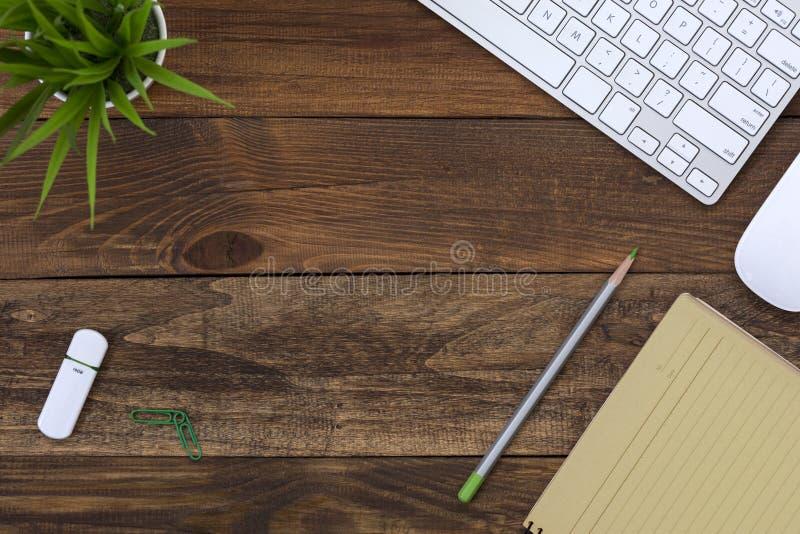 Ξύλινη θέση εργασίας άποψης επιτραπέζιων κορυφών με την κίτρινη σελίδα εγγράφου στοκ φωτογραφίες