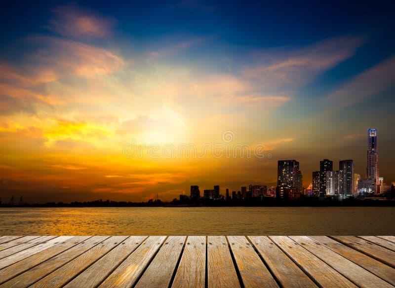 Ξύλινη διάβαση πεζών και πόλη στο υπόβαθρο ηλιοβασιλέματος στοκ εικόνες
