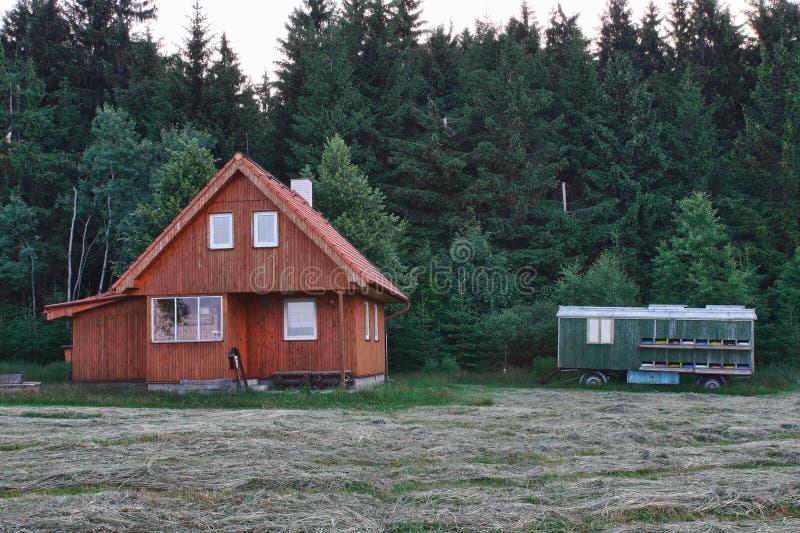 Ξύλινη καμπίνα κούτσουρων κοντά στο δάσος στη νεφελώδη ημέρα και το κινητό ασβέστιο μεταφορών στοκ εικόνα με δικαίωμα ελεύθερης χρήσης