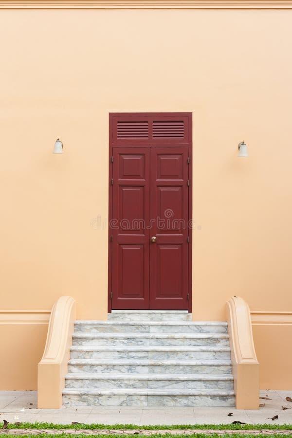 Ξύλινη καφετιά πόρτα στον πορτοκαλή τοίχο στοκ φωτογραφίες με δικαίωμα ελεύθερης χρήσης