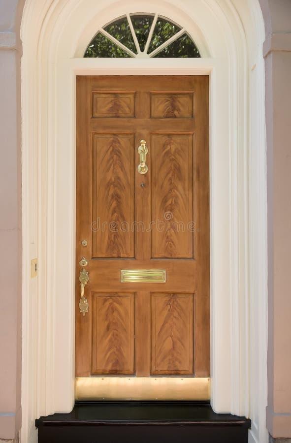 Ξύλινη μπροστινή πόρτα της οικογενειακής κατοικίας με την αψίδα στοκ εικόνες