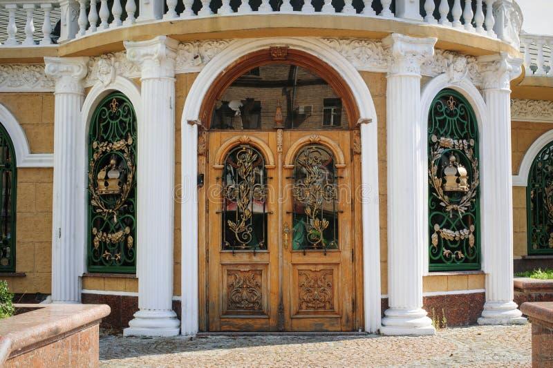 Ξύλινη πόρτα με τη σφυρηλατημένη σχάρα μετάλλων στοκ εικόνα