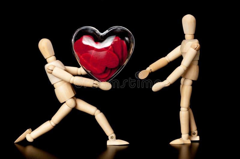 Ξύλινη πλαστή κόκκινη καρδιά εκμετάλλευσης που απομονώνεται στοκ φωτογραφία