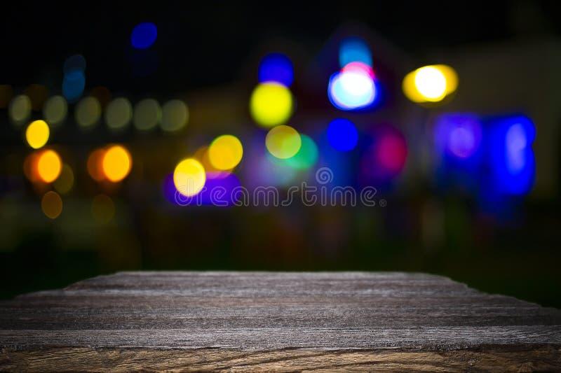 Ξύλινη πλατφόρμα γραφείων και bokeh τη νύχτα στοκ φωτογραφία