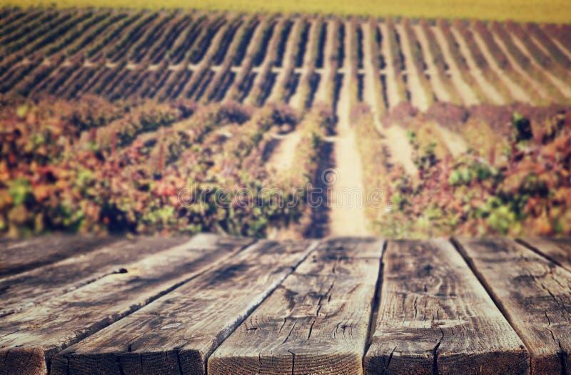 Ξύλινοι αγροτικοί πίνακες μπροστά από το υπόβαθρο αμπελώνων το φθινόπωρο έτοιμος για την επίδειξη προϊόντων στοκ εικόνα