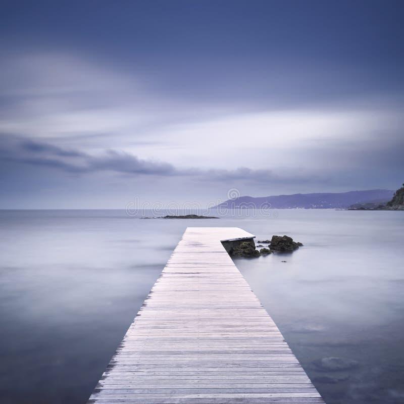 Ξύλινοι αποβάθρα, βράχοι και θάλασσα στο misty ηλιοβασίλεμα στοκ εικόνες με δικαίωμα ελεύθερης χρήσης