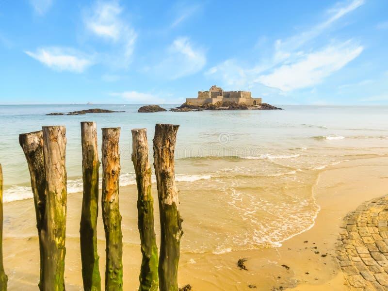 Ξύλινοι κυματοθραύστες στη χαμηλή παλίρροια και οχυρό εθνικό στοκ φωτογραφίες