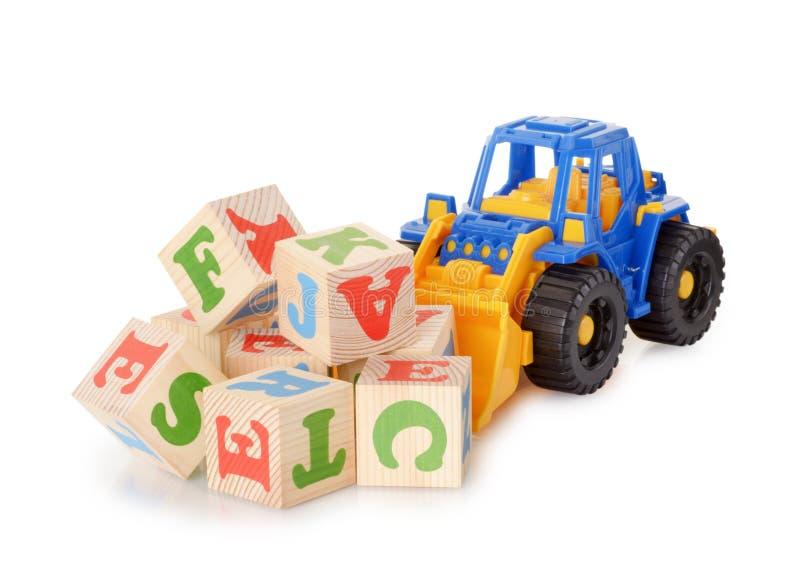 Ξύλινοι φραγμοί αλφάβητου με ένα τρακτέρ παιχνιδιών στοκ εικόνα