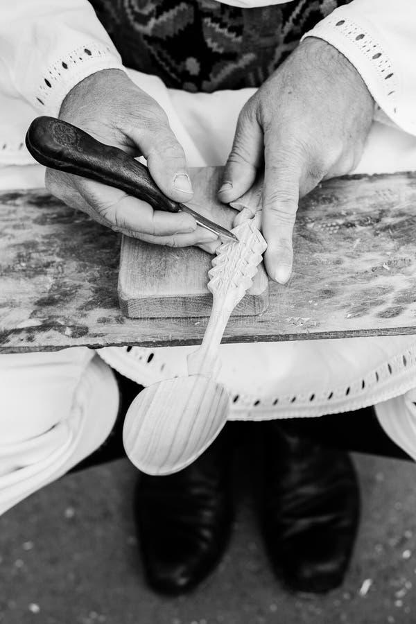 ξύλινοι χαράζοντας sculpting ρουμανικοί βιοτέχνες κουταλιών στοκ φωτογραφίες