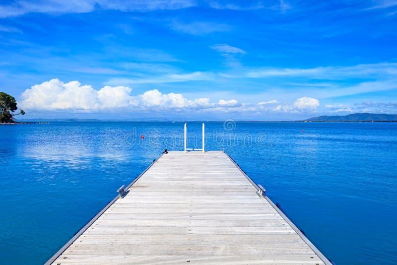 Ξύλινος αποβάθρα ή λιμενοβραχίονας σε έναν μπλε ωκεανό. Παραλία σε Argentario, Τοσκάνη, Ιταλία στοκ φωτογραφίες
