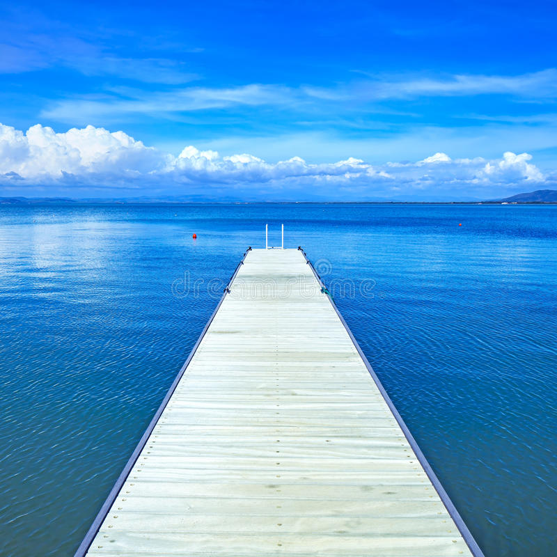 Ξύλινος αποβάθρα ή λιμενοβραχίονας σε έναν μπλε ωκεανό. Παραλία σε Argentario, Τοσκάνη, Ιταλία στοκ εικόνα