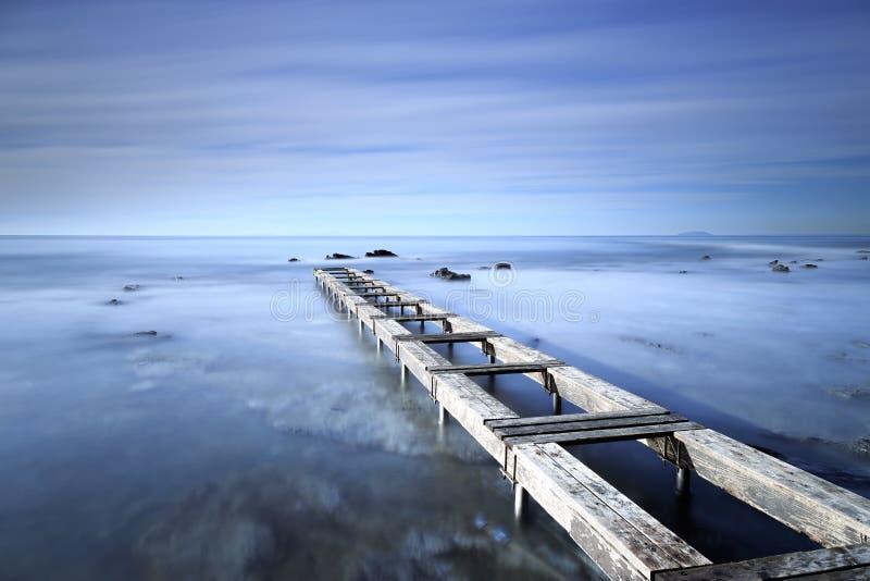 Ξύλινος αποβάθρα ή λιμενοβραχίονας σε έναν μπλε ωκεανό το πρωί Μακρύ Exposur στοκ φωτογραφία με δικαίωμα ελεύθερης χρήσης