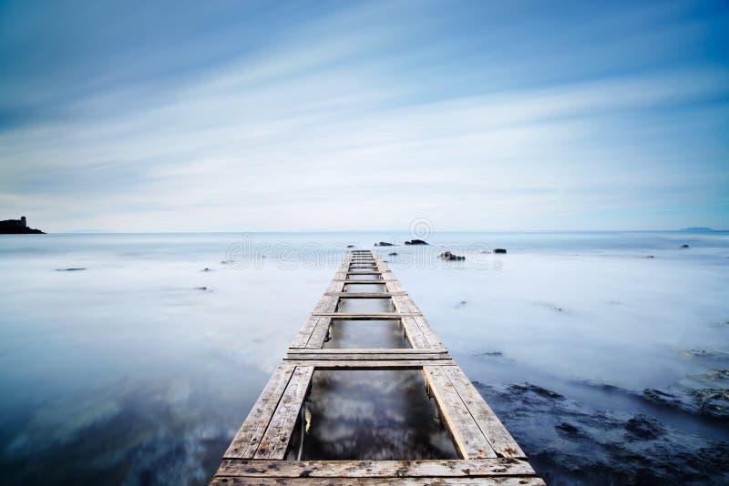 Ξύλινος αποβάθρα ή λιμενοβραχίονας σε έναν μπλε ωκεανό το πρωί Μακρύ Exposur στοκ φωτογραφίες