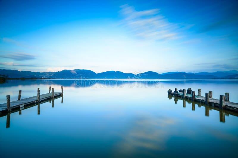 Ξύλινος αποβάθρα δύο ή λιμενοβραχίονας και σε ένα μπλε ηλιοβασίλεμα και έναν ουρανό λιμνών refle στοκ φωτογραφία με δικαίωμα ελεύθερης χρήσης