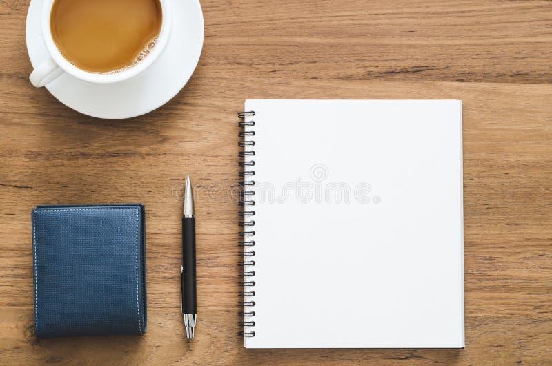 Ξύλινος πίνακας γραφείων με το κενά σημειωματάριο, τη μάνδρα, το πορτοφόλι και το φλυτζάνι ομο στοκ εικόνες με δικαίωμα ελεύθερης χρήσης