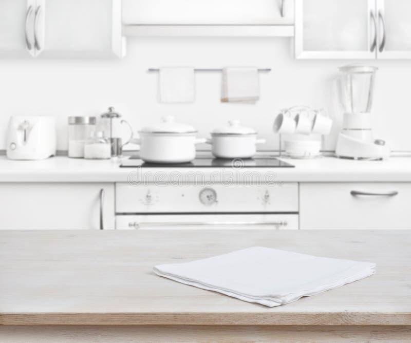Ξύλινος πίνακας με την πετσέτα στο θολωμένο άσπρο σύγχρονο υπόβαθρο κουζινών στοκ φωτογραφία με δικαίωμα ελεύθερης χρήσης