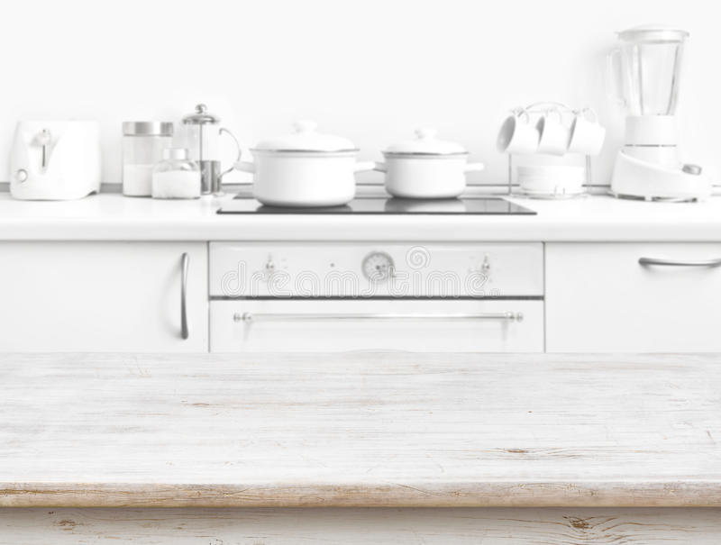 Ξύλινος πίνακας μπροστά από το θολωμένο άσπρο εσωτερικό πάγκων κουζινών στοκ φωτογραφία με δικαίωμα ελεύθερης χρήσης