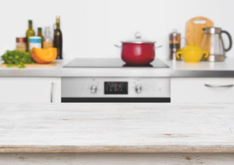 Ξύλινος πίνακας στην εστίαση στο θολωμένο άσπρο εσωτερικό υπόβαθρο κουζινών στοκ φωτογραφία