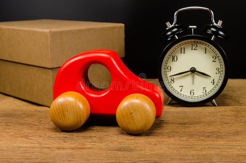 ξύλινο αυτοκίνητο παιχνιδιών και αναδρομικό ξυπνητήρι στοκ εικόνες