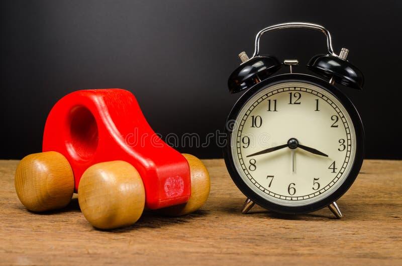 ξύλινο αυτοκίνητο παιχνιδιών και αναδρομικό ξυπνητήρι στοκ φωτογραφίες με δικαίωμα ελεύθερης χρήσης