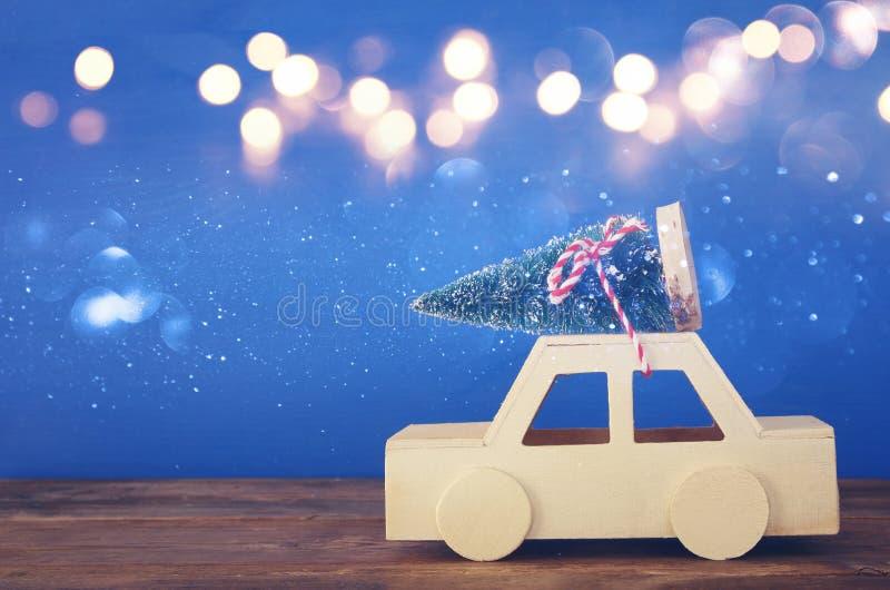 Ξύλινο αυτοκίνητο που φέρνει ένα χριστουγεννιάτικο δέντρο στον πίνακα στοκ εικόνες