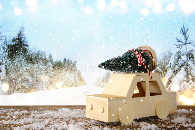 Ξύλινο αυτοκίνητο που φέρνει ένα χριστουγεννιάτικο δέντρο στοκ φωτογραφία