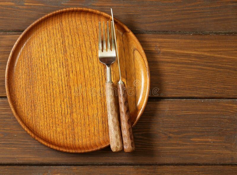 Ξύλινο κενό πιάτο σε ένα ξύλινο υπόβαθρο στοκ φωτογραφίες