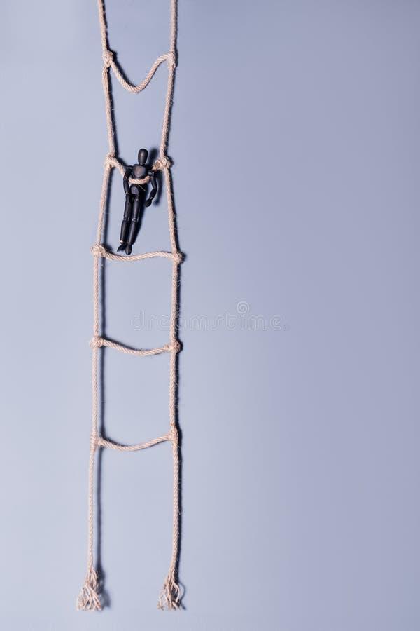 Ξύλινο μελαχροινό μανεκέν που στέκεται στην κρεμώντας σκάλα σχοινιών στο μπλε υπόβαθρο Έννοια ζωής Εκλεκτική εστίαση στοκ εικόνα
