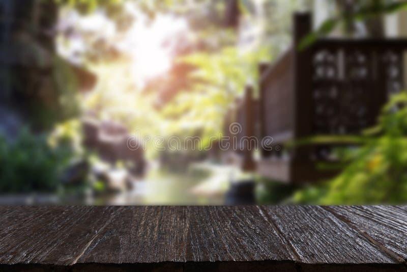 ξύλινο μπαλκόνι εκτός από τη λίμνη στον κήπο με τον ξύλινο πίνακα για την επίδειξη ο στοκ φωτογραφία με δικαίωμα ελεύθερης χρήσης