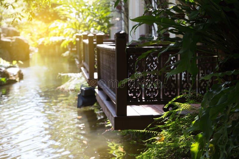 ξύλινο μπαλκόνι εκτός από τη λίμνη στον κήπο στοκ εικόνα
