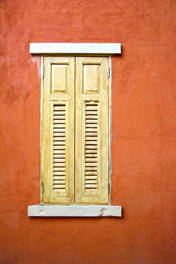 Ξύλινο παράθυρο στο πορτοκαλί υπόβαθρο τοίχων στοκ φωτογραφία με δικαίωμα ελεύθερης χρήσης