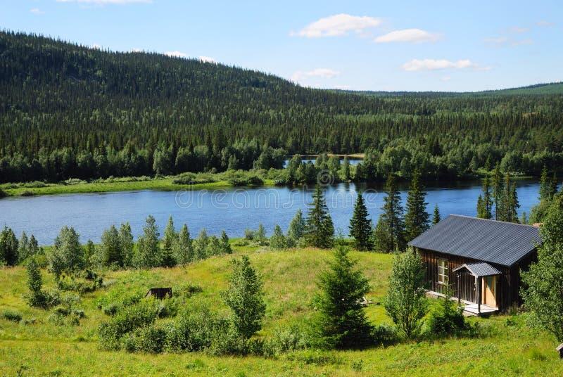 Ξύλινο σπίτι κοντά στην μπλε λίμνη στη μέση του δάσους taiga. στοκ φωτογραφία με δικαίωμα ελεύθερης χρήσης