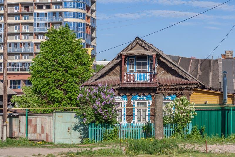 Ξύλινο σπίτι κούτσουρων κάτω από την κατασκευή στο υπόβαθρο των πολυκατοικιών Οδός Iaroslavskaia, Cheboksary, Chuvash Δημοκρατία, στοκ εικόνες με δικαίωμα ελεύθερης χρήσης