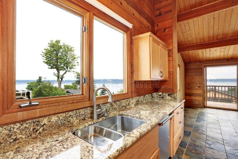 Ξύλινο σπίτι περιποίησης με το ανοικτό σχέδιο ορόφων Κουζίνα με την αντίθετη κορυφή γρανίτη στοκ εικόνες