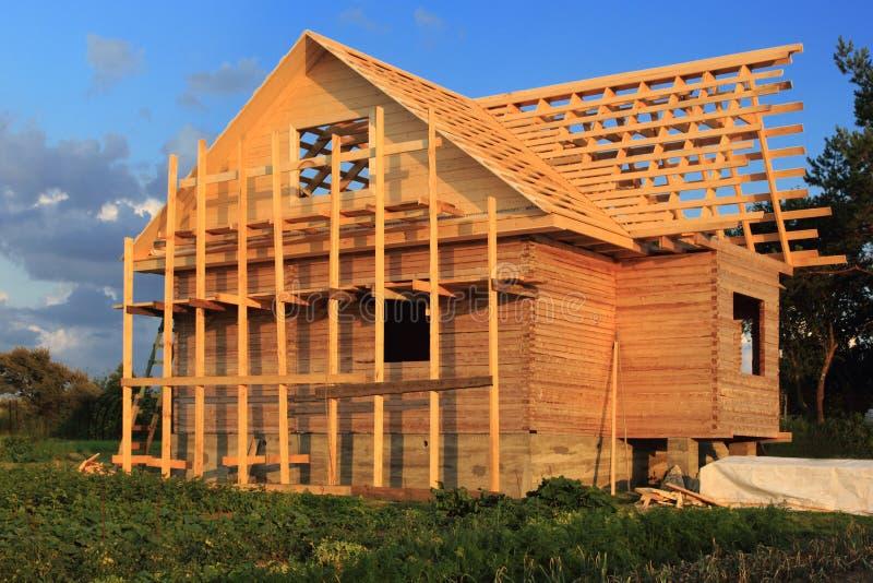 Ξύλινο σπίτι στα υλικά σκαλωσιάς κάτω από την κατασκευή στοκ φωτογραφία με δικαίωμα ελεύθερης χρήσης