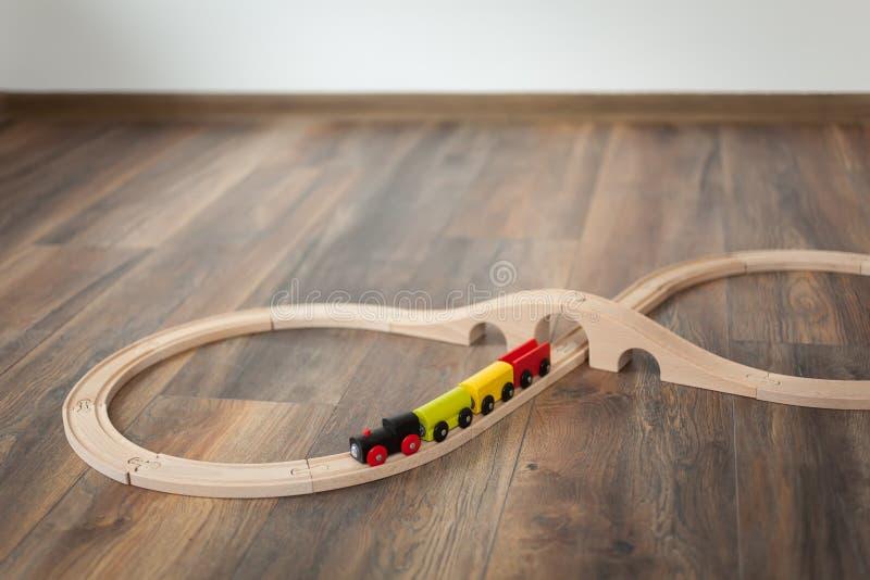 Ξύλινο τραίνο παιχνιδιών στο σιδηρόδρομο με την ξύλινη γέφυρα Καθαρίστε το τοποθετημένο σε στρώματα πάτωμα στοκ φωτογραφίες