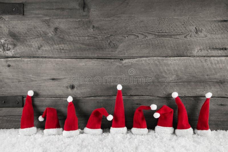 Ξύλινο υπόβαθρο Χριστουγέννων με τα κόκκινα καπέλα santa για ένα εορταστικό FR στοκ εικόνες