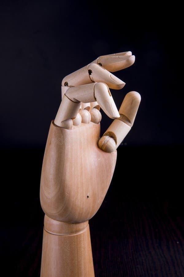 Ξύλινο χέρι σε ένα σκοτεινό υπόβαθρο στοκ εικόνα