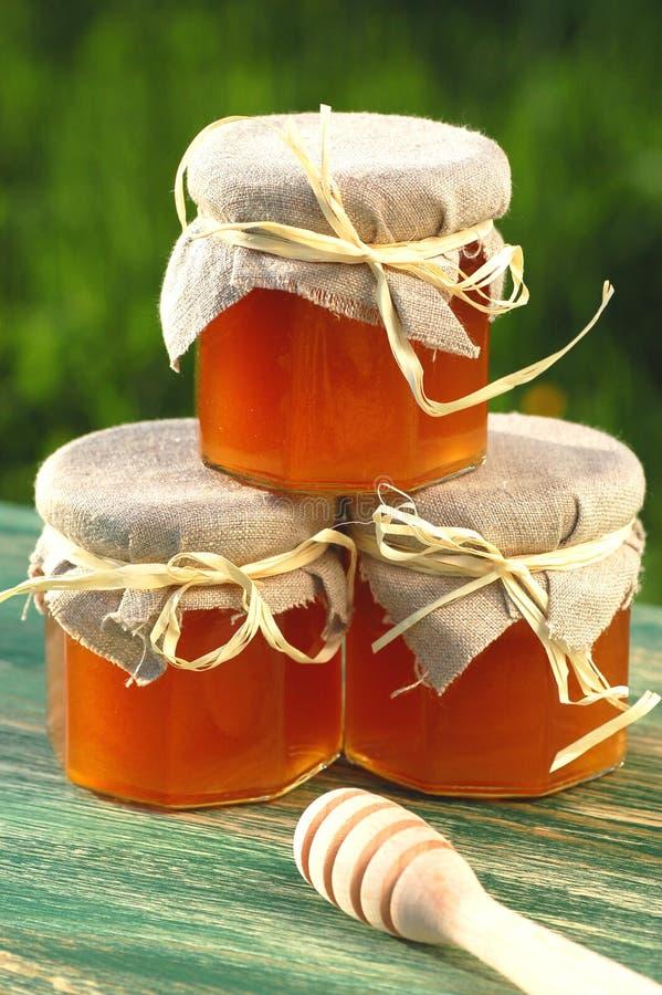 Ξύλινο dipper μελιού και σύνολο βάζων του εύγευστου φρέσκου μελιού στο μελισσουργείο στοκ εικόνες