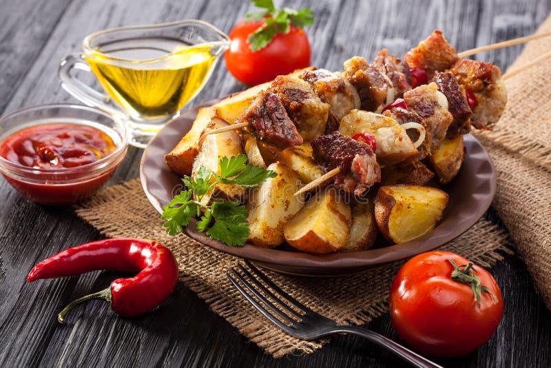 Οβελίδιο κρέατος με τα χορτάρια με τα κρεμμύδια, τις ψημένες πατάτες, τις ντομάτες και τα πράσινα στοκ φωτογραφίες