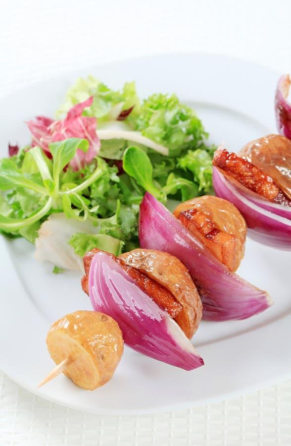 Οβελίδιο μπέϊκον και πατατών με τα πράσινα σαλάτας στοκ φωτογραφία