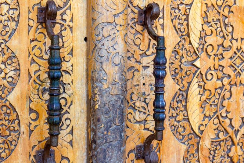 ογκώδης ξύλινη μπροστινή πόρτα με τις λαβές μετάλλων επεξεργασμένου σιδήρου στο ασιατικό ύφος στοκ εικόνα