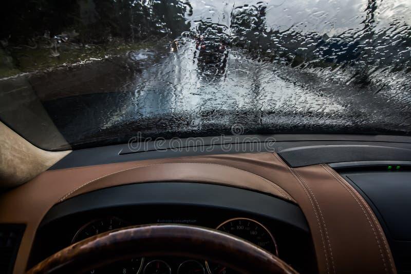 Οδήγηση αυτοκινήτων στη βροχή άποψη από το εσωτερικό σταγόνες βροχής στον ανεμοφράκτη Φτωχή διαφάνεια και επικίνδυνη οδήγηση στοκ εικόνα