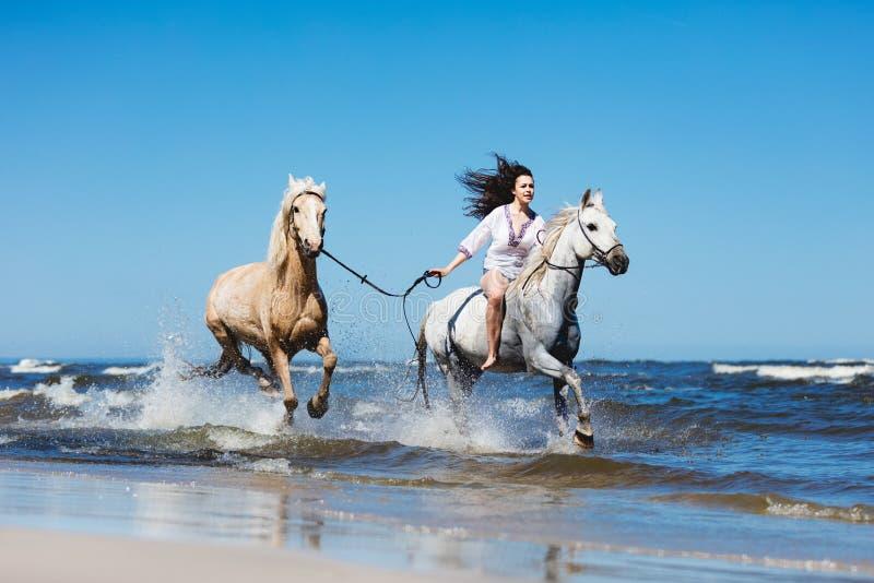 Οδήγηση κοριτσιών μέσω της θάλασσας με δύο άλογα στοκ εικόνες